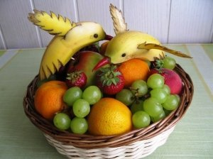 Vaisių ir uogų krepšelis su bananiniais paukščiais